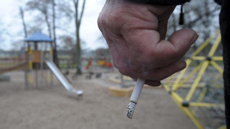 Ein Mann hält auf einem Spielplatz eine Zigarette in der Hand. Foto: Peter Endig/dpa-Zentralbild/dpa/Archivbild