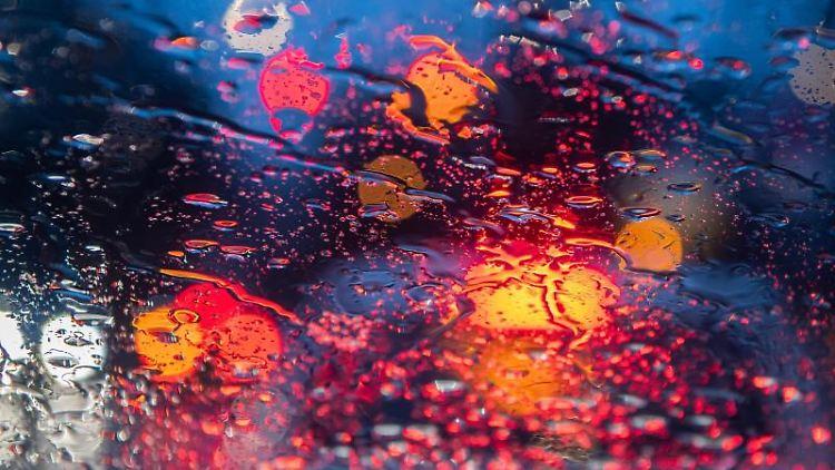 Regentropfen sind am Morgen im Berufsverkehr auf einer Autoscheibe zu sehen. Foto: Robert Michael/dpa-Zentralbild/ZB/Archivbild