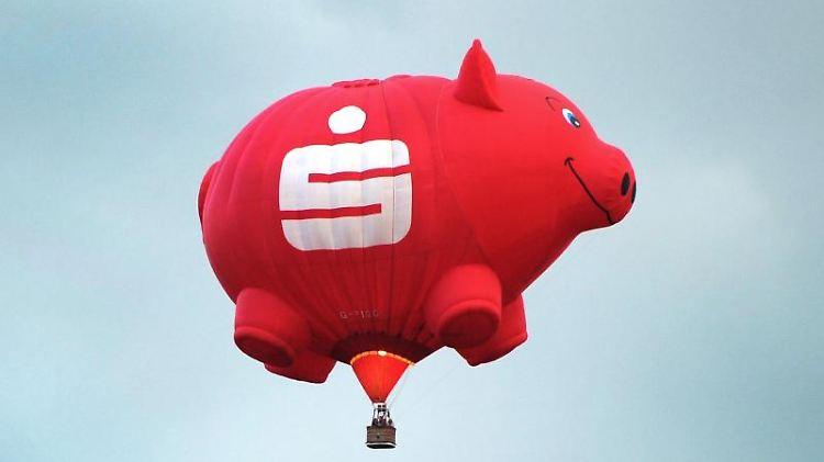 Ein Heißluftballon in der Form eines Sparschweines mit einem Sparkassen-Logo ist am Himmel zu sehen. Foto: Daniel Naupold/dpa/Archivbild