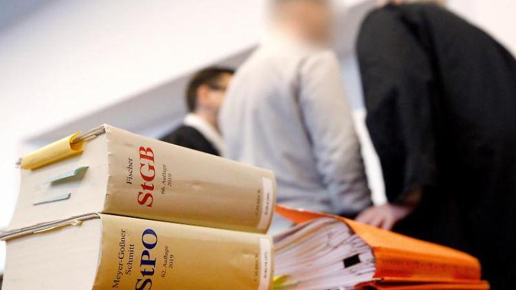 Der Hauptangeklagte (M) unterhält sich vor Prozessbeginn mit seinen Anwälten. Foto: Roland Weihrauch/dpa
