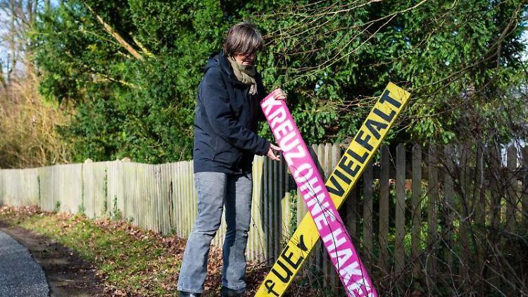 Eine Anwohnerin stellt ein Holzkreuz mit der Aufschrift
