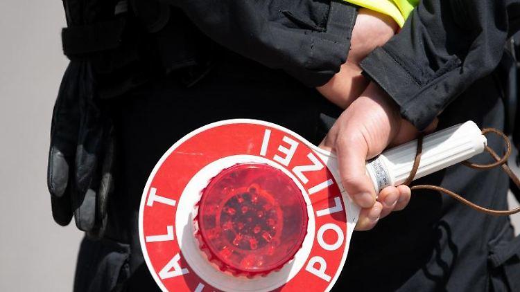 Ein Polizist hält eine Kelle in den Händen. Foto: Sven Hoppe/dpa/Archiv