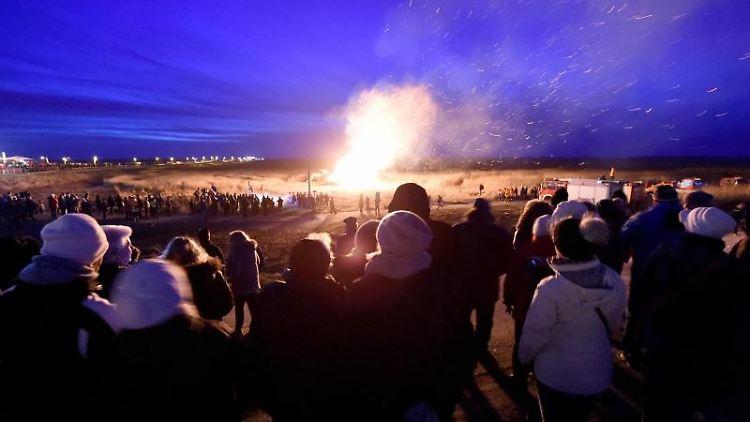 Besucher stehen am Strand vor dem Biikefeuer. Foto: Carsten Rehder/dpa/Archivbild