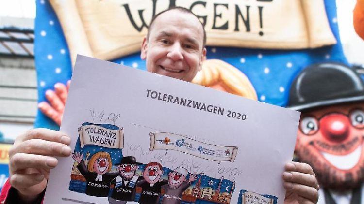 Jacques Tilly hält den Entwurf für den Toleranzwagen in den Händen. Foto: Federico Gambarini/dpa