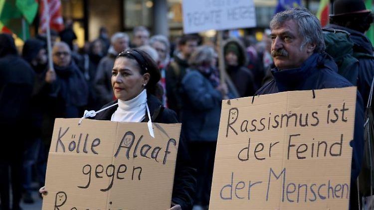 Mit Plakaten nehmen Kölner Bürger an einer Kundgebung von
