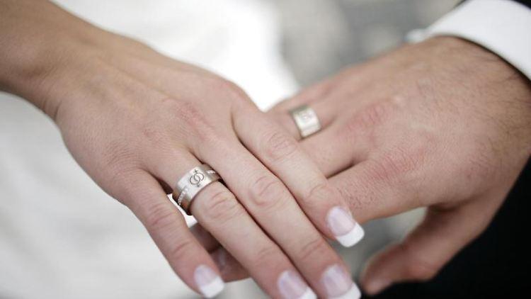 Zwei frisch Vermählte legen nach einer Trauung die Hände ineinander. Foto: picture alliance / Jörg Carstensen/dpa/Archivbild