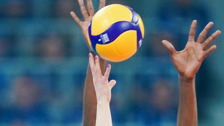 Arme strecken sich in Richtung des Volleyball. Foto: Uwe Anspach/dpa/Archivbild