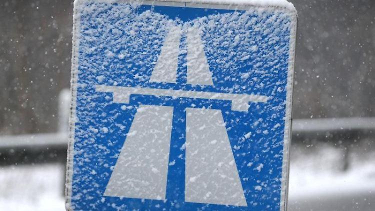 Ein Autobahnschild ist von Schnee bedeckt. Foto: David Young/dpa/Archivbild