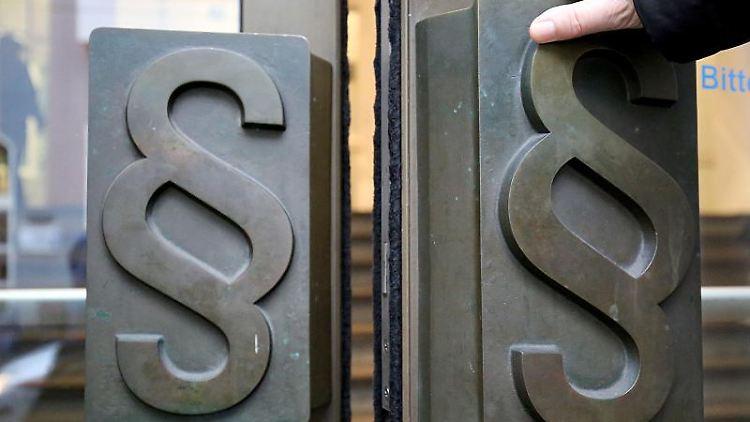 Paragrafen-Symbole sind an Türgriffen am Eingang zu einem Gericht angebracht. Foto: Oliver Berg/dpa/Archivbild