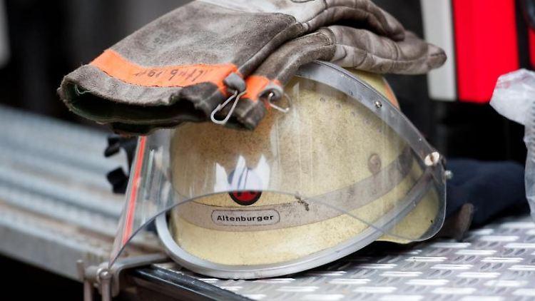 Ein Feuerwehrhelm liegt an einem Einsatzfahrzeug. Foto: picture alliance/dpa/Archivbild