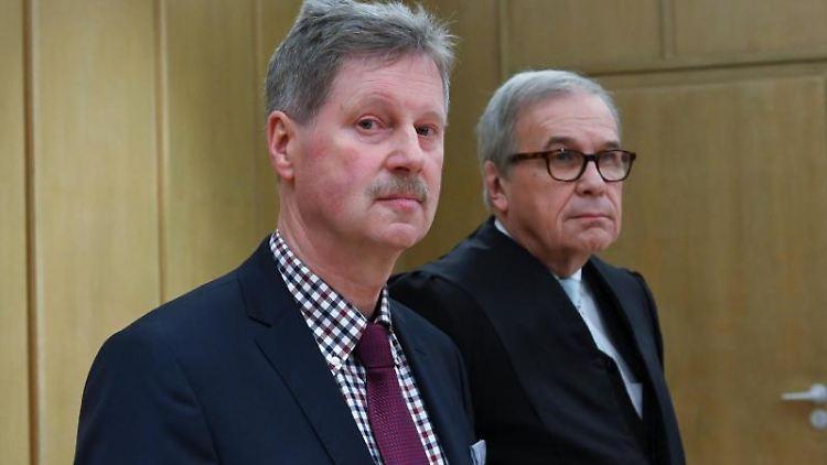 Klemens Olbrich (l), Bürgermeister von Neukirchen, steht zu Prozessbeginn im Amtsgericht neben seinem Anwalt Karl-Christian Schelzke. Foto: Uwe Zucchi/dpa/Archivbild