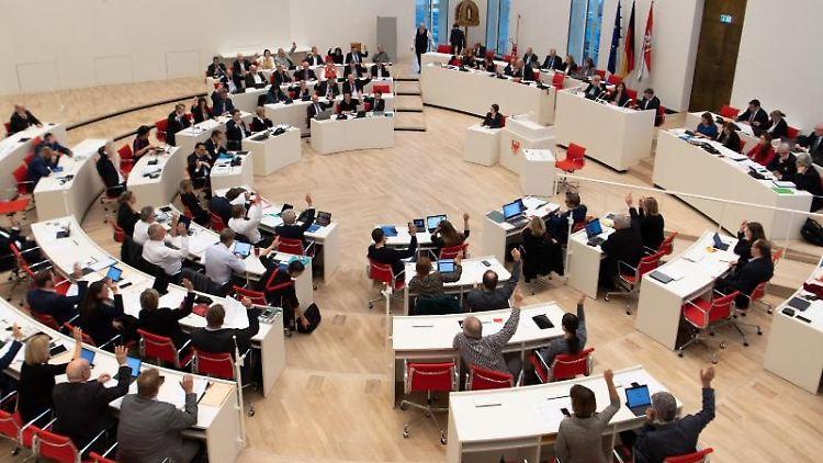 Abgeordnete nehmen im Landtag an einer Abstimmung per Handzeichen teil. Foto: Monika Skolimowska/dpa-Zentralbild/dpa/Archivbild