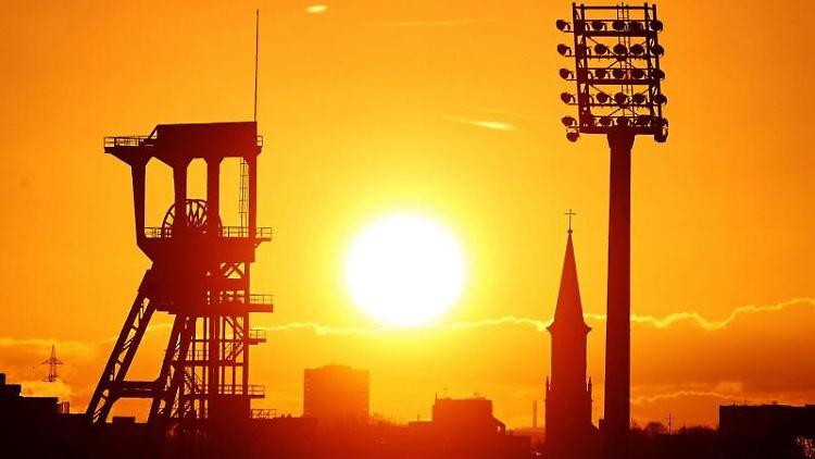 Die Sonne geht über dem Förderturm der Zeche Holland und einem Flutlichtmast des Lohrheidestadion auf. Foto: Bernd Thissen/dpa/Archivbild