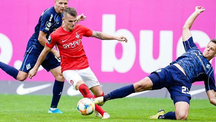 Kaiserslauterns Florian Pick (M) kämpft in der Saison 2018/19 um den Ball mit Mannheims Dorian Diring (l) und Mannheims Michael Schultz. Foto: Uwe Anspach/dpa/Archivbild