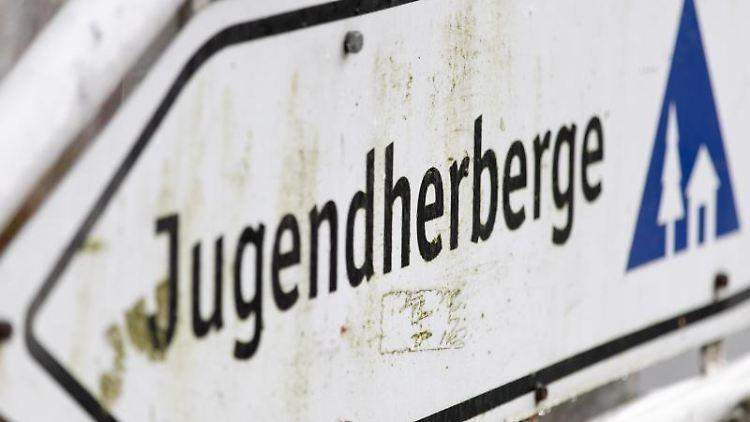 Blick auf einen Wegweiser vor einer Jugendherberge. Foto: Friso Gentsch/dpa/Archiv