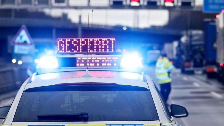 Auf einem Polizeifahrzeug leuchtet die Aufschrift