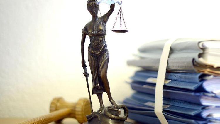 Eine modellhafte Nachbildung der Justitia steht neben einem Holzhammer und einem Aktenstapel. Foto: Volker Hartmann/dpa/Archiv