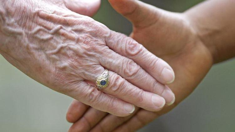 Zwei Personen geben sich die Hand. Foto: Uwe Anspach/dpa/Archiv