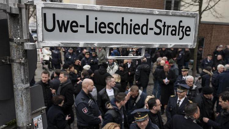 Besucher versammeln sich um das neue Straßenschild der Uwe-Lieschied-Straße in Neukölln. Foto: Fabian Sommer/dpa