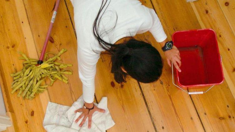 Eine Frau putzt den Fußboden. Foto: Ralf Hirschberger/dpa-Zentralbild/dpa/Archivbild