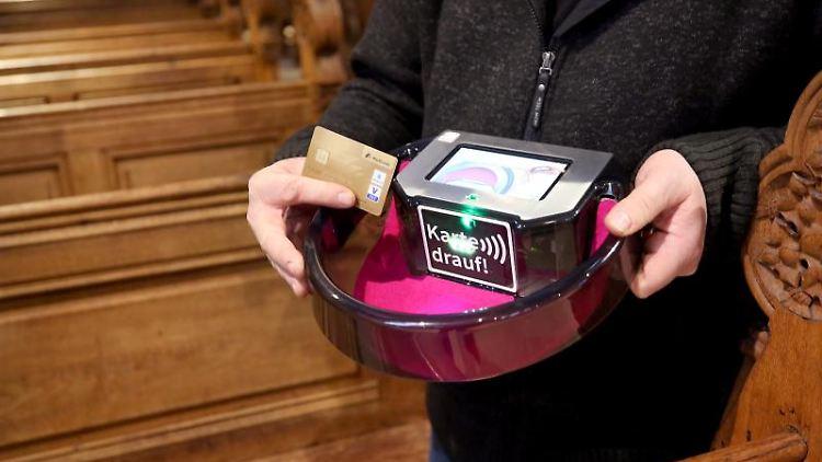 Den digitalen Kollektenkorb demonstriert Küster Holger Kanaß in der Salvatorkirche. Foto: Roland Weihrauch/dpa