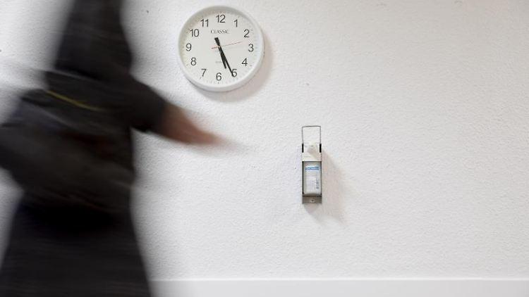 Eine Uhr und ein Desinfektionsmittelspender hängen an einer Wand in einem Krankenhaus. Foto: Christoph Soeder/dpa/Archivbild