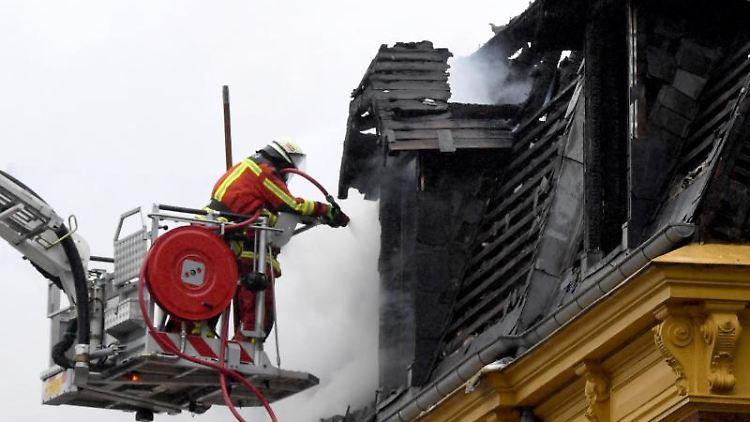 Feuerwehrleute bekämpfen Glutnester nach einem Brand in einem Mehrfamilenhaus. Foto: Carsten Rehder/dpa