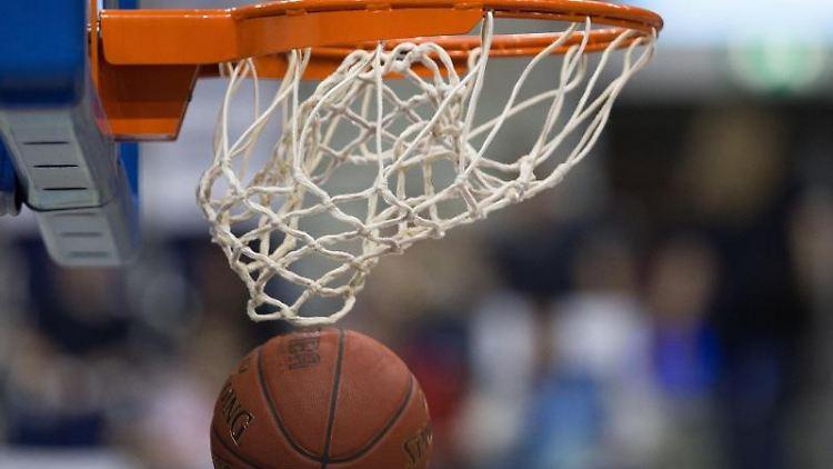 Ein Basketball fällt durch das Netz vom Basketballkorb. Foto: Lukas Schulze/dpa/Archivbild