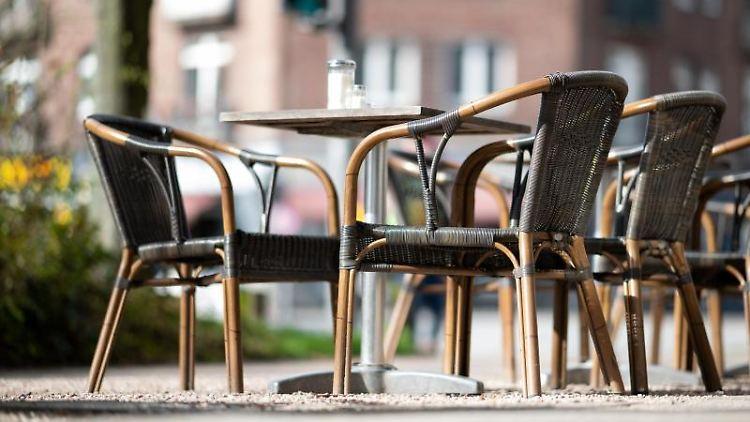 Leere Stühle vor einem Café. Foto: Daniel Reinhardt/dpa
