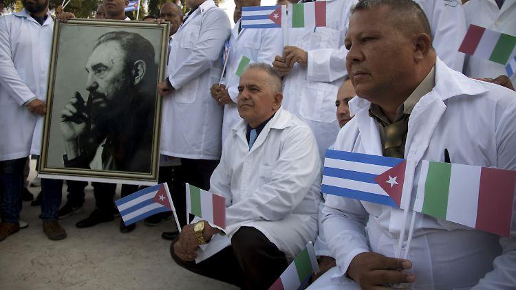 Kubanische Hilfskräfte lassen sich mit einem Foto von Fidel Castro, sowie kubanischen und italienischen Landesflaggen vor ihrer Reise nach Italien fotografieren.