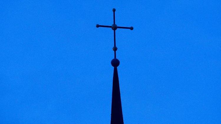 Ein Kreuz in der Abenddämmerung. Foto: Friso Gentsch/dpa/Symbolbild