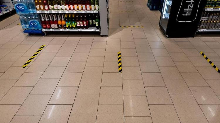 Markierungsband im Abstand von 1,50 Meter ist auf den Fußboden in einem Supermarkt geklebt. Foto: Robert Michael/dpa-Zentralbild/dpa