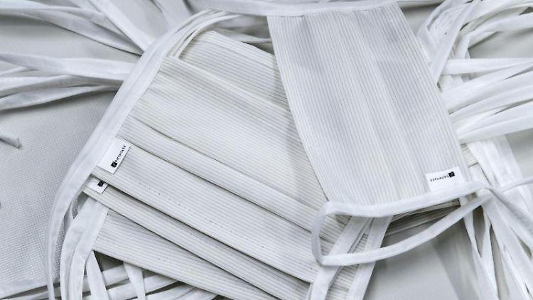 Mundschutzmasken liegen auf einem Tisch. Foto: Hendrik Schmidt/dpa-Zentralbild/ZB