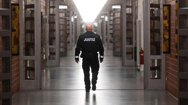 Ein Justizbeamter geht über einen langen Flur in der Justizvollzugsanstalt Sehnde. Foto: Julian Stratenschulte/dpa/Archivbild