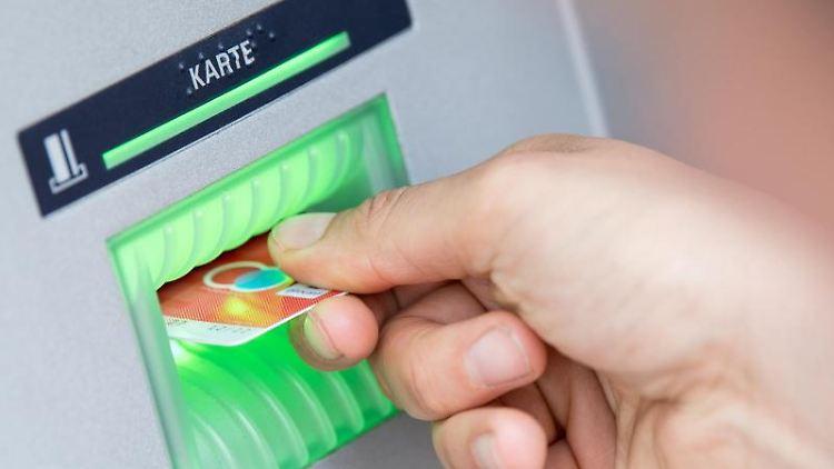 Eine Bankkundin steckt ihre Girokarte in einen Geldautomaten. Foto: Fabian Sommer/dpa/Archivbild
