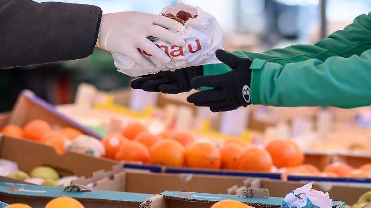 Ein Markthändler gibt mit Handschuhen eine Tüte an eine Kundin. Foto: Sebastian Gollnow/dpa