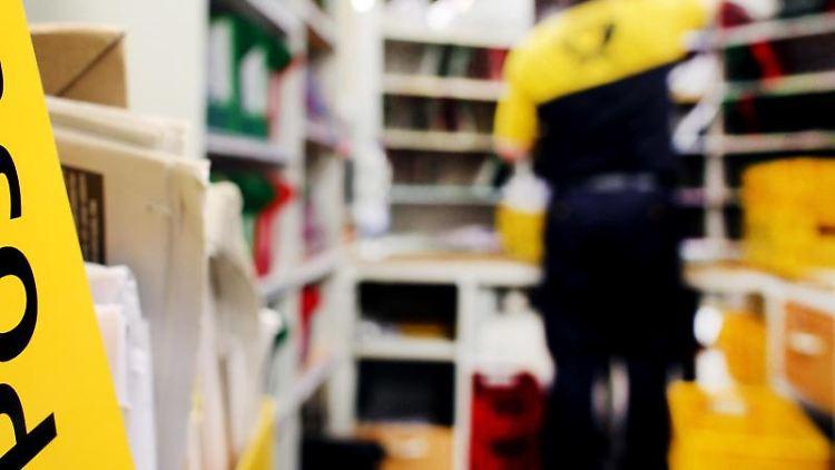 Ein Mitarbeiter der Post sortiert im Briefverteilzentrum die Post. Foto: picture alliance / Oliver Berg/dpa/Symbolbild