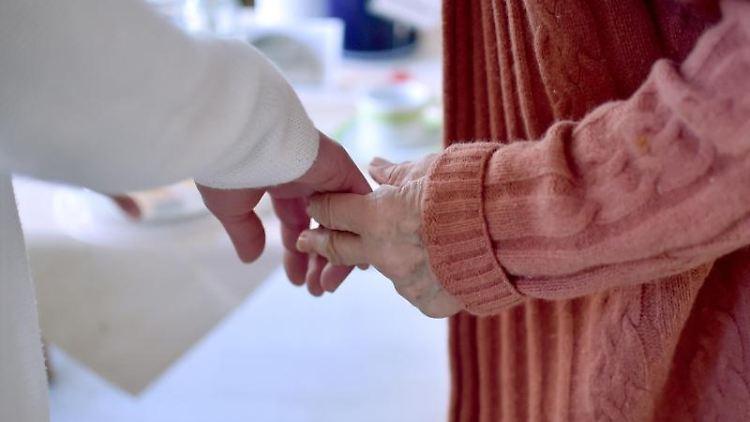 Eine Pflegekraft hält die Hand einer Bewohnerin einer Pflegeeinrichtung. Foto: Britta Pedersen/dpa-Zentralbild/dpa/Symbolbild