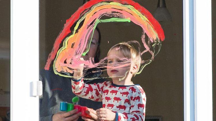 Tom malt gemeinsam mit seiner Mutter Monika Kabus einen Regenbogen an ein Fenster. Foto: Oliver Dietze/dpa
