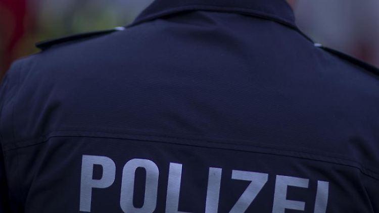 Ein Polizist steht vor einem Polizeifahrzeug. Foto: Jens Büttner/dpa-Zentralbild/ZB/Symbolbild