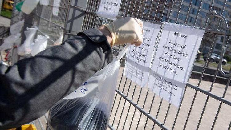 Ein Mann hängt eine Tüte an einen Zaun am Marienplatz. Foto: Marijan Murat/dpa