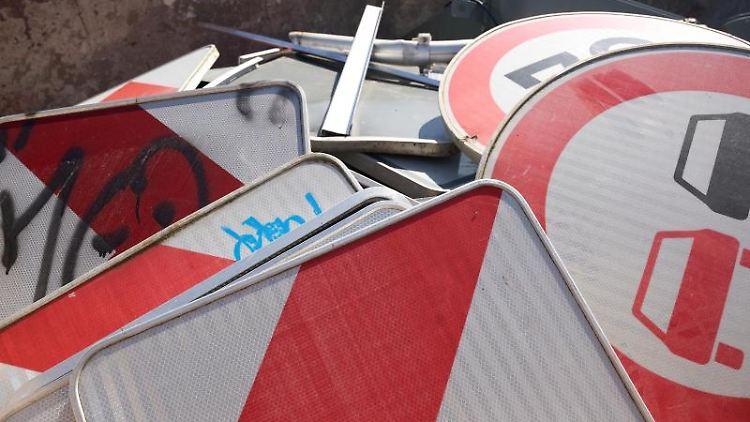 Beschmierte, verbogene und ausgebleichte Verkehrsschilder liegen in einem Schrottcontainer. Foto: Thomas Frey/dpa