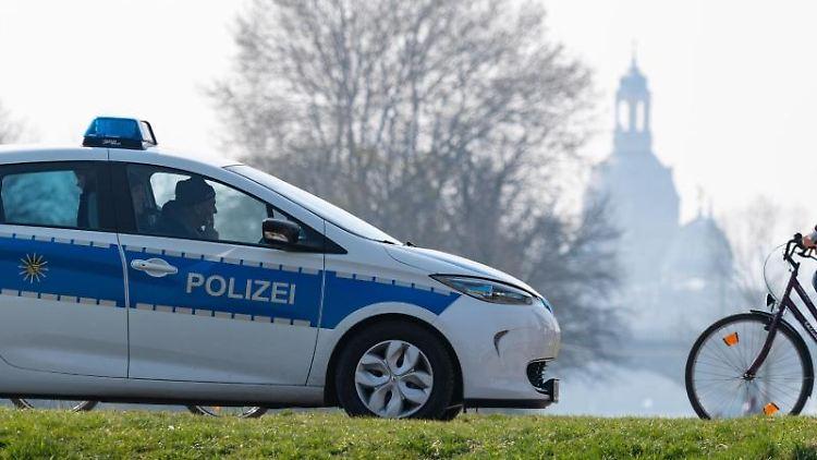 Ein Polizeiauto am Elberadweg mit der Frauenkirche im Hintergeund. Foto: Robert Michael/dpa-Zentralbild/dpa