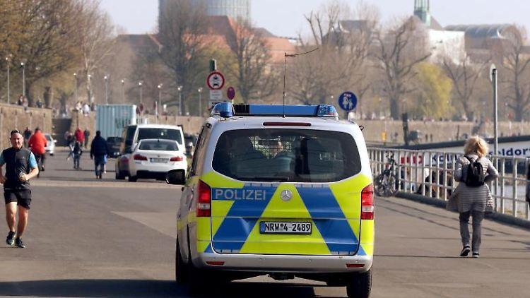 Die Polizei kontrolliert am Rheinufer in Düsseldorf die Einhaltung der Corona-Vorsichtsmaßnahmen. Foto: David Young/dpa