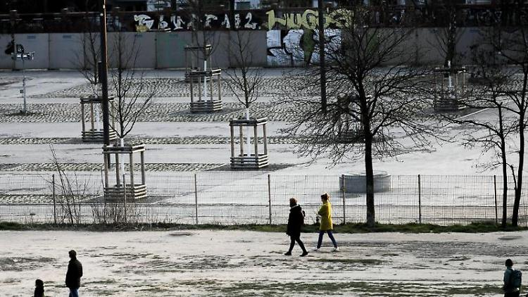 Menschen gehen im Mauerpark mit großem Abstand zueinander spazieren. Foto: Carsten Koall/dpa