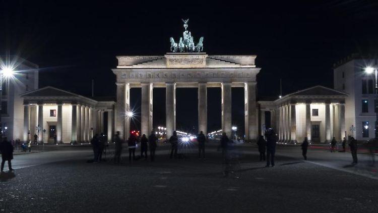 Das Brandenburger Tor leuchtet kurz vor Beginn der Earth Hour. Foto: Paul Zinken/dpa
