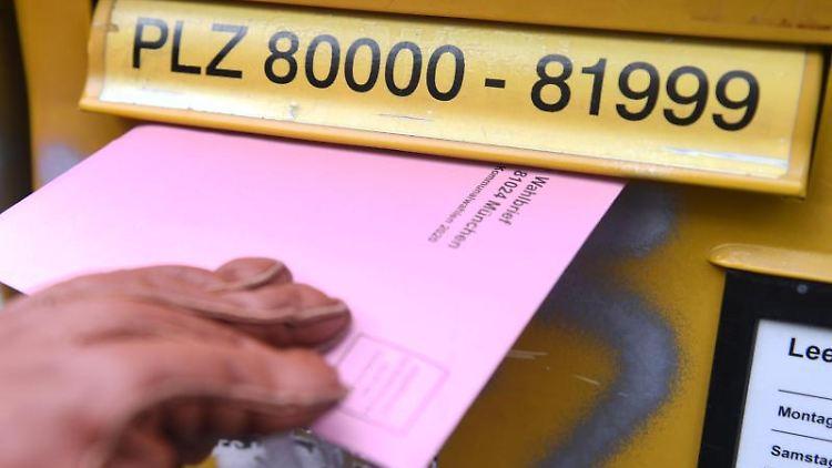 Eine Frau mit den Briefwahlunterlagen für die Kommunalwahl 2020 vor einem Briefkasten. Foto: Felix Hörhager/dpa/Archivbild