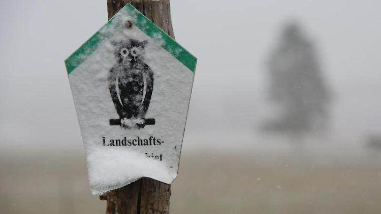 Blick auf ein verschneites Hinweisschild vor einem Feld in Hasselfelde. Foto: Matthias Bein/dpa-Zentralbild/ZB