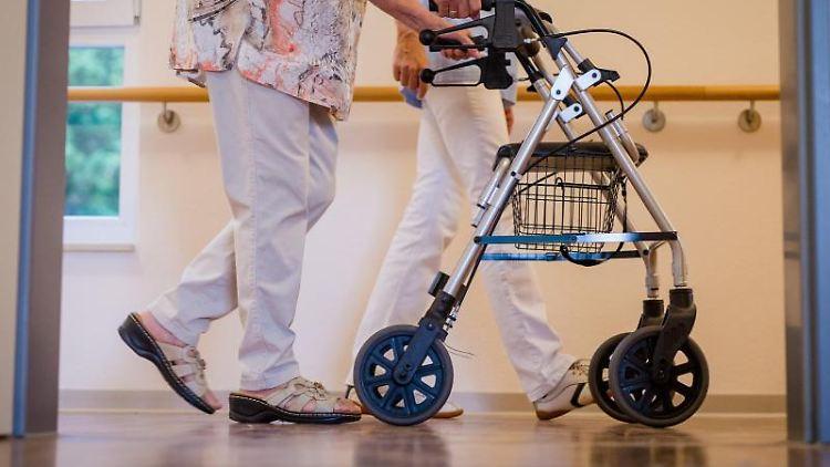 Eine Pflegekraft geht in einem Pflegeheim mit einer älteren Dame über einen Korridor. Foto: Christoph Schmidt/dpa/Symbolbild