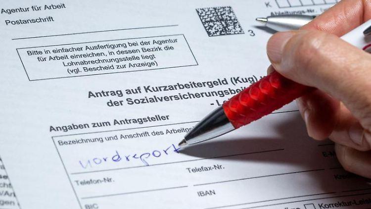 Eine Frau füllt ein Antragsformular für Kurzarbeitergeld aus. Foto: Jens Büttner/dpa/Illustration